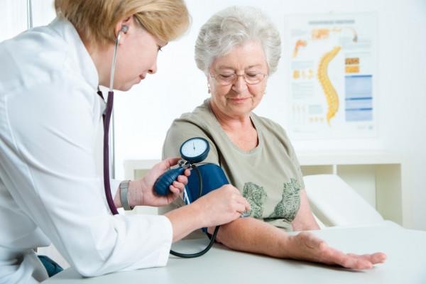 Mujer tomando tensión arterial por una enfermera