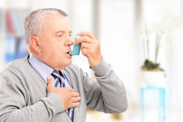 Hombre que trata el asma con inhalador